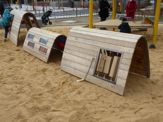 kleine Spieltunnel mit Klangelementen, Drehhölzern und farbigen Fenstern