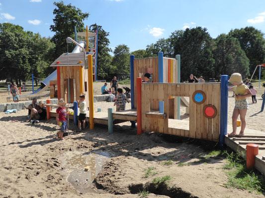 Spielsteg mit Sandkränen, Sieben, Spielwänden und Kistenhäusern