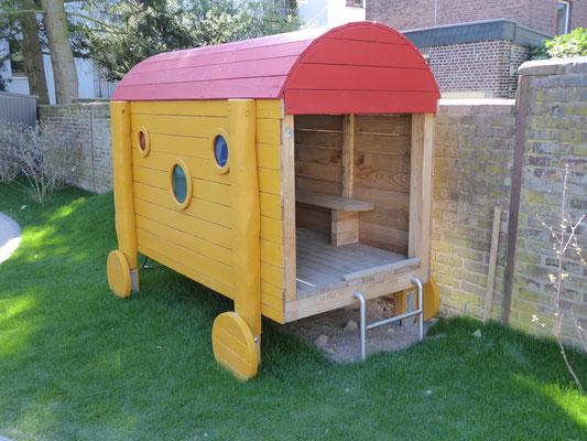kleiner Bauwagen mit Bänkchen und farbigen Fenstern