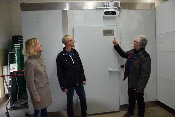 Uta Lutze und Jürgen Amediek von der Stiftung lassen sich von Pastor Heinrich Friesen die Kühlanlage zeigen. (v.l.)