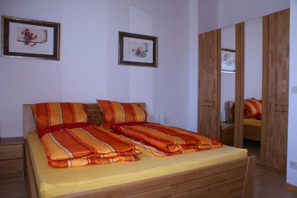 Doppelbett im separaten Schlafzimmer im Obergeschoss