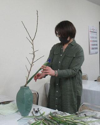 梅の面白い枝ぶりを活かし、アイリスを挿し添えるMichikoさん。