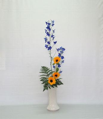 2019.7.9 <デルフィニウム 向日葵 レザーファン> Kayoさんの作品です。シンプルにスッキリとまとめられたと思います。夏に飾りたい作品です。