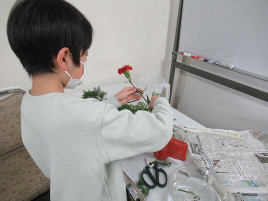 クリスマスに似合いそうな花器を選び、花材と合わせながら考えていけているRikuくん。