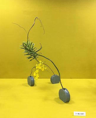 Kumikoさんの作品です。石化柳の枝ぶりを活かしてオンシジウムとドラセナ・インディアナとの出合いの美しさをダイナミックに表現しています。