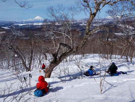 2021.3.13 気持ちの良い澄んだ空気の中、前方に浮かぶ羊蹄山を眺めながらの休憩。野外とはいえソーシャルディスタンスをとりながら昼食を摂る。