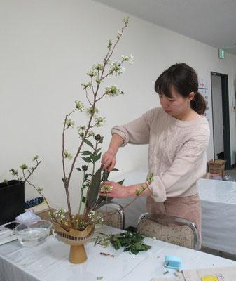 傾いている桜の枝をバランスよく剣山に挿すのに苦労しているQianさん。
