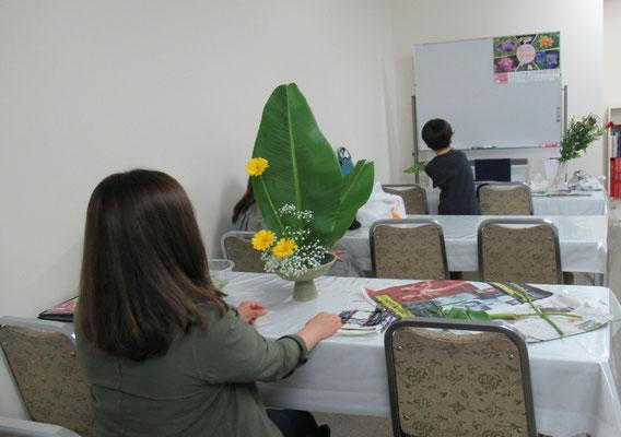 2019.7.3 お花を始めてまだ3ケ月のYayoiさん。お花屋さんから届いた糸芭蕉をいけ終えた背中が語っているものは? 私には力を尽くして格闘技を闘い終えたような雰囲気?に見えました。お疲れ様!
