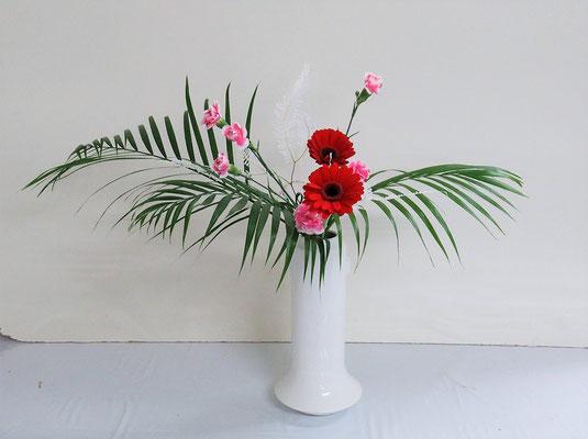 2021.2.3 <アレカヤシ ガーベラ スプレーカーネーション 晒し山シダ> Ittsuちゃんの作品です。ガーベラは滑りやすいし花首もくらくらしていて留めにくい花材ですが、集中を切らさずよく頑張りましたね。
