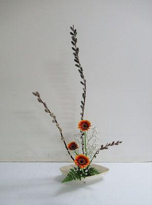 2021.2.24 <バッコ柳 ガーベラ かすみ草 レザーファン> Naokoさんの作品です。里の春を思わせるバッコ柳の芽の膨らみが柔らかです。