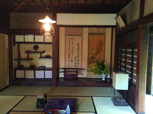農村群にある旧岩間家の客間。床の間にしつらえられた白磁の器はどことなく韓国の時代劇に出てきそうで、いけばなも厳かな雰囲気。傍らに置かれた日本刀が武家の出身であることを示している。