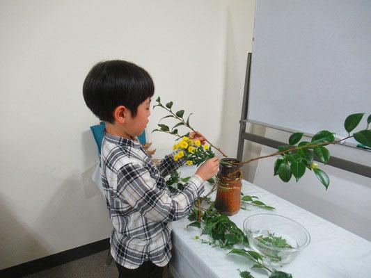 小さな蕾や余分な花を丁寧に整理するRikuくん。