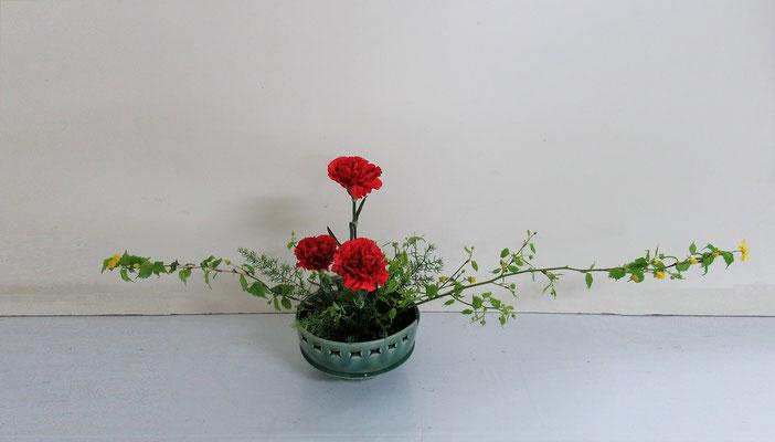 2019.5.15 <山吹 アスパラガス・スプレンゲリ カーネーション> Akikoさんの作品です。「主材は山吹でもスプレンゲリでもいいので考えてみてね」とお話しして、出来上がったのがこの作品。初級者にとって花材の取合せを見て表現方法を考えるのは難しいことですが、このような経験が知らず知らずのうちに自分の身に付き力となっていくことでしょう。