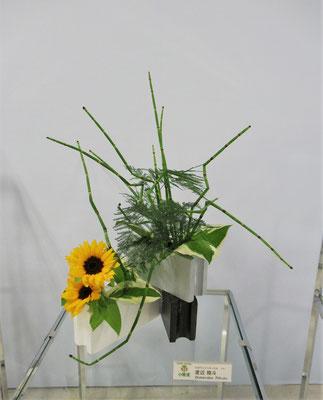 Rikuくんの作品です。初めての花展ですが、器に見立てるものを探して構想を練りました。作品を観ていると、楽しくいけたのが弾けて伝わるようです。Rikuくんは小学四年生です。