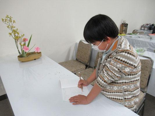 出来上がった作品を見ながらスケッチするIttsuちゃん。花材の名前も随分憶えてくれています。