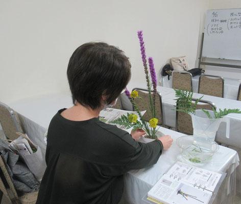 手際よく花材に鋏を入れ、葉の表情を考えるKaoruさん。