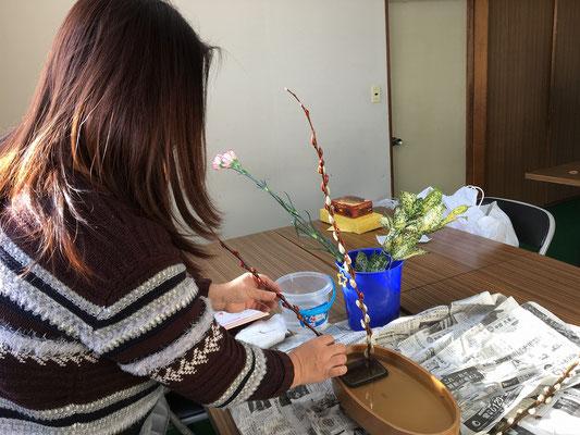 初めての盛花。小判型水盤に直立型のお稽古です。副枝の位置づけを考えるMichiyoさん。