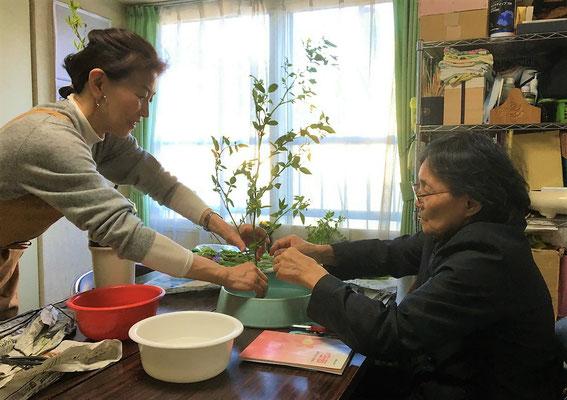 枝が硬く剣山に挿しにくそうでしたので、Atsukoさんがサポート。