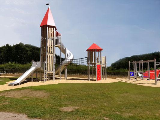 Abenteuerspielplatz mit Tunnelrutsche, Hängebrücke und Kletterwand.