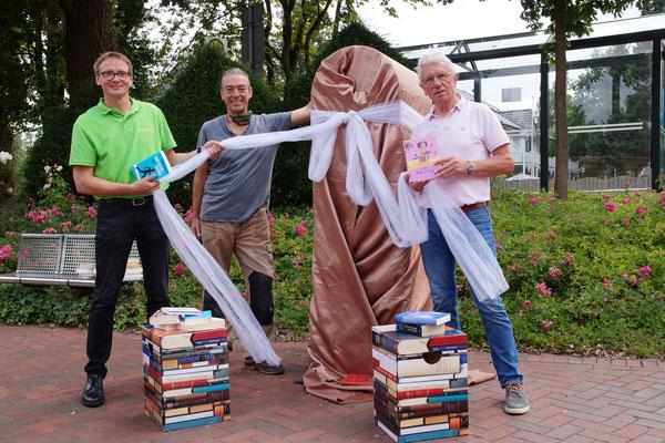 Der neue Bücherschrank ist noch verpackt und wartet auf seine Enthüllung  (von links): Johannes Geers (Kommunalmanager bei Westenergie), Friedrich-Ralf Faulenbach (Installateur Bücherschrank) und Bruno Matzke (Bücherschrank Pate und zweiter Bürgermei