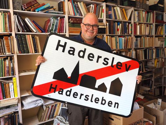 Die Diskussion um die Zweisprachigkeit hält bis heute an - René Rasmussen mit Entwurf für ein zweisprachiges Ortsschild. Foto: C. Schumann, 2020