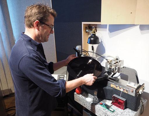 """Peter Wendler legt eine Lackmatritze in Lasergerät – daraus wird ein """"Negativ"""" für die Plattenpresse.  Peter Wendler legt eine Lackmatritze in Lasergerät – daraus wird ein """"Negativ"""" für die Plattenpresse. Foto: C. Schumann, 2020"""
