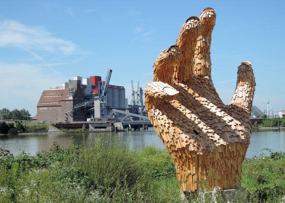 Überlebensgroße Holzhand des Künstlerkollektivs Kalihara, im Hintergrund der historische Rethe-Speicher. Foto: Christoph Schumann, 2020