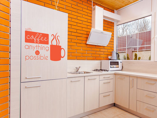 With Coffee anything is possible wall art sticker on a kitchen fridge.