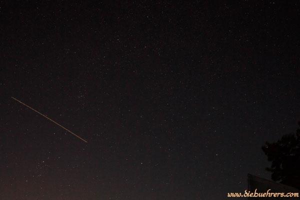 Blick in den Nachthimmel, links ein Flugzeug