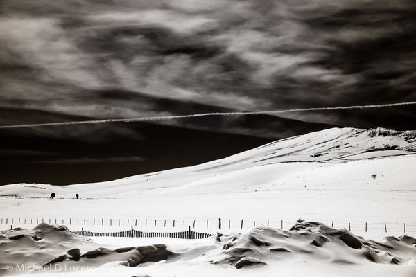 Winter snowfield cut with contrail in the sky. Photographed with infrared converted camera. Central Utah