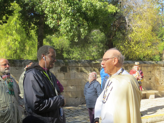 The custodian priest at St Anne's speaking with Bishop Louis