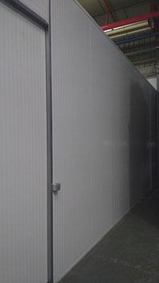 Detalle de pared en panel sandwich blanco, con puerta corredera