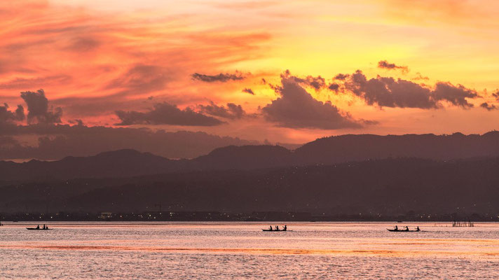 Cebu at sunset with 3 fisherman on their boats