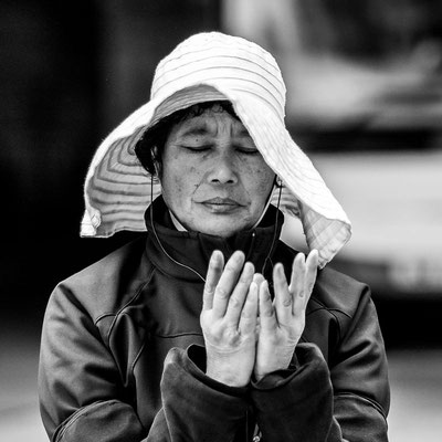 Photo of a woman praying in the street