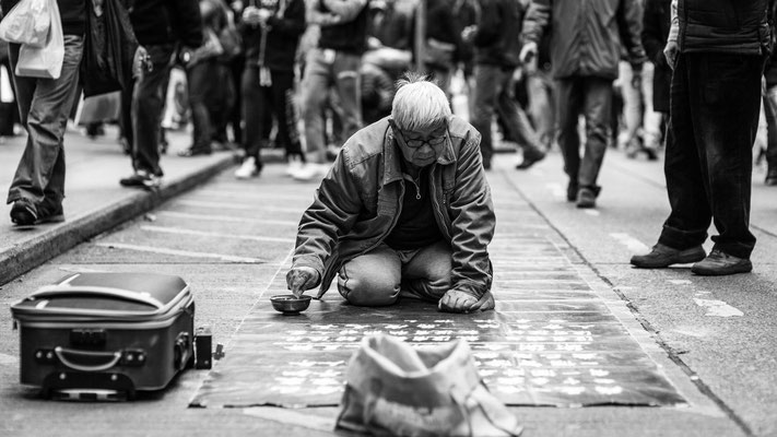 Photo of a man writing with sand on the street