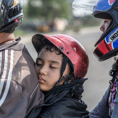 Photo of a young sleeping boy on a motorbyke