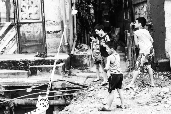 Photo of kids in the street playing with throwing stones in the hole