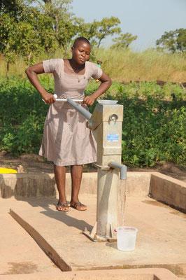 Eine Schülerin pumpt am Wasserbrunnen