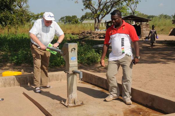 Pfarrer Renner probiert den neuen Wasserbrunnen aus