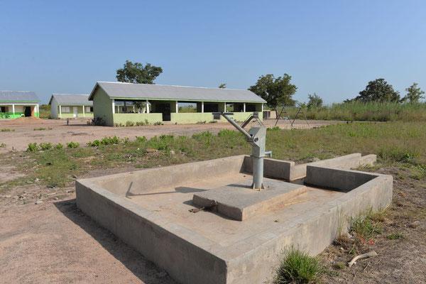 Ein neuer Brunnen am Schulgelände, im Hintergrund die Gebäude der Junior High School