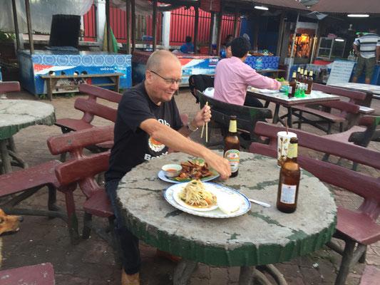 Gegrilltes Huhn (mit Stäbchen) und Papaya-Salat auf dem Nachtmarkt