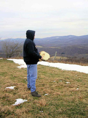 Playing one of the lightning-struck hickory drums while standing on the mountain.