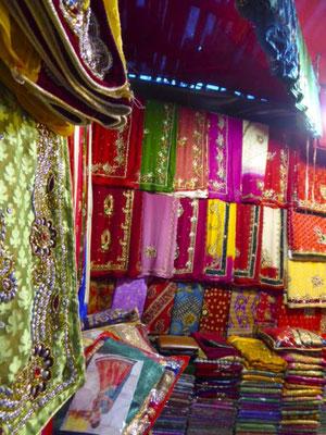 auf dem neben moderner Kleidung auch viele bunte Sari verkauft werden.