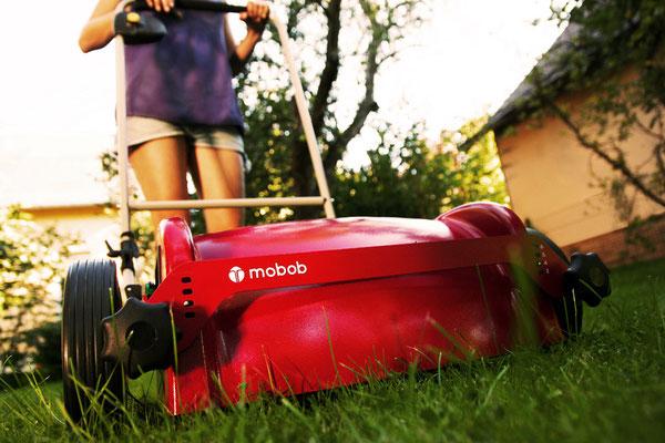 Frau mäht mit Mulchmäher mobob® den Rasen