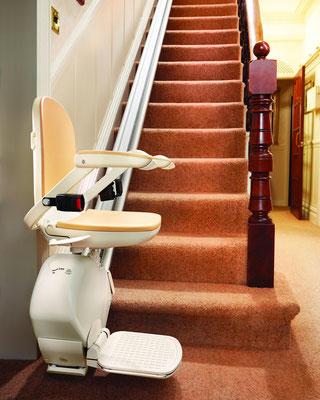 Treppenlift am unteren Haltepunkt. So kann der Nutzer platznehmen und nach oben fahren.