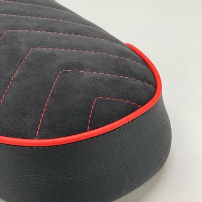 Die roten Ziernähte und der farblich passende Keder runden das sportliche Gesamtbild ab.