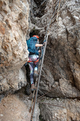 Climbing on the ladders on the north face of Torre di Toblin