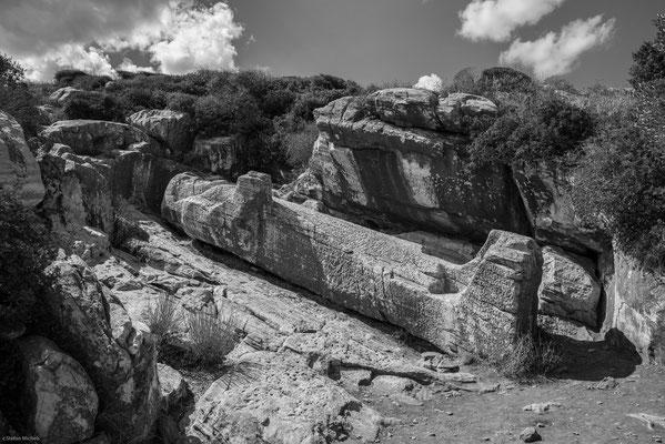 Drei antike, aus dem rohen Stein gehauene, unvollendete monolithische Kolossalstatuen sogenannte Jünglinge (Kouroi) liegen noch heute in Steinbrüchen aus der archaischen Zeit.