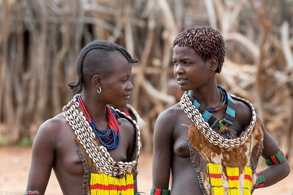 Frauen tragen dünn geflochtene halblange Zöpfe.
