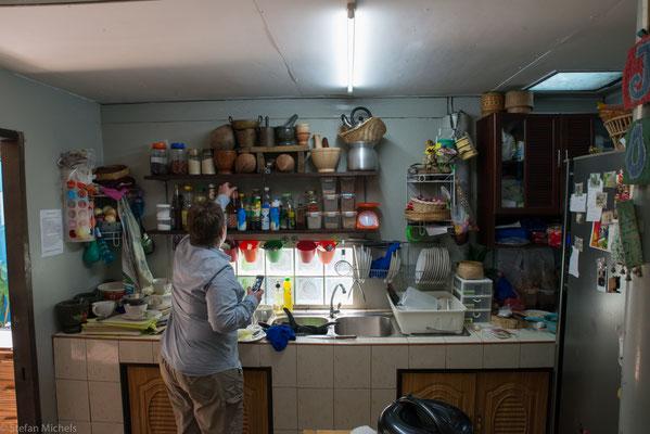Auf dem Tisch stehen vier Gaskochherde, je einer für zwei Kursteilnehmer. Poo zeigt die Zutaten, erklärt die Zubereitung, kocht das Gericht schwupdiwupp vor.